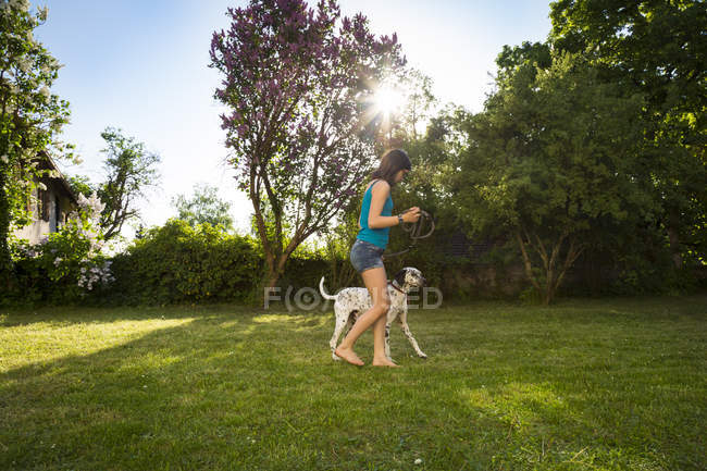 Girl with Dalmatian in the garden — Stock Photo