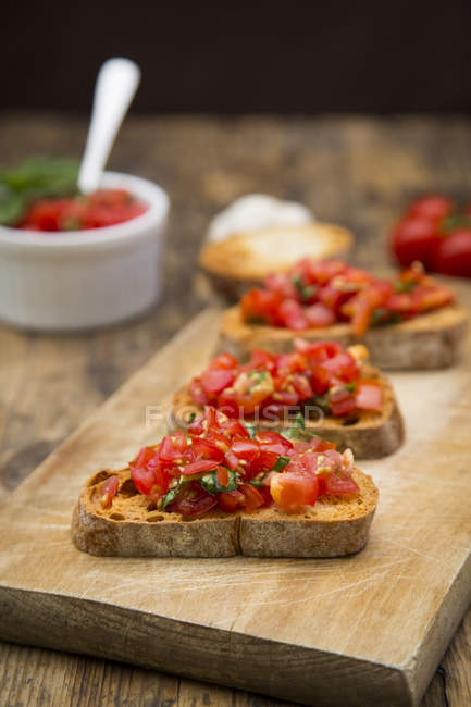Bruschetta with tomatoes and basil on wooden board, close up — Stock Photo