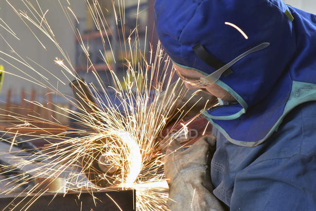 Worker using angle grinder in factory — Stock Photo