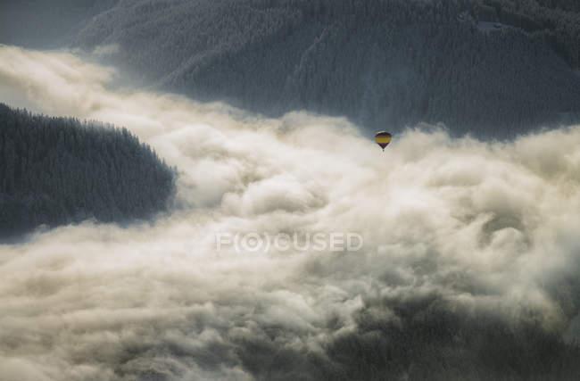 Austria, Salzkammergut, Hot air balloon over clouds in alpine landscape — стоковое фото