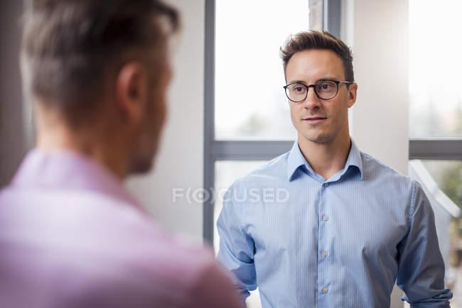 Zwei Geschäftsleute unterhalten sich am Fenster — Stockfoto