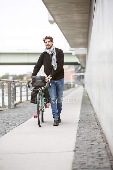 Homme souriant poussant vélo sur un chemin — Photo de stock