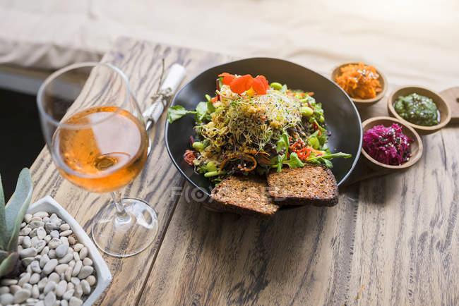 Dekorierte Salatschüssel auf Holztisch mit Glas Rosenwein — Stockfoto