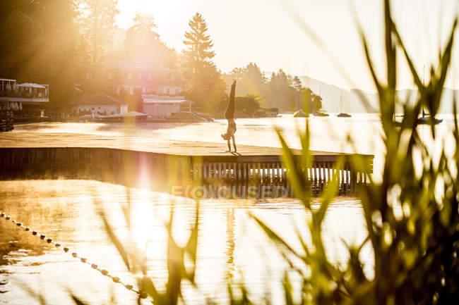 Donna che pratica yoga sul molo al lago e facendo stand — Foto stock