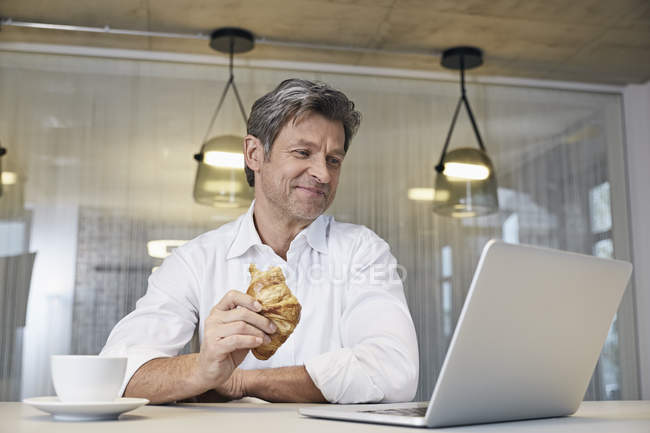 Businessman using laptop while eating croissant — Stock Photo