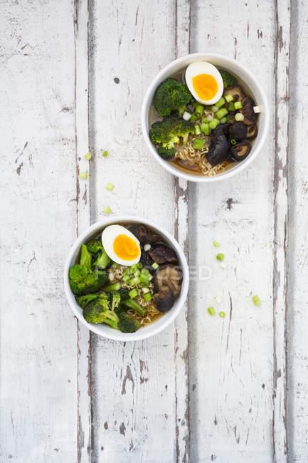 Deux bols de soupe Ramen avec oeuf, brocoli, nouilles, champignons shitake et oignons de printemps — Photo de stock