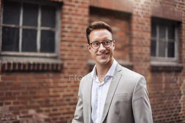 Ritratto di giovane uomo d'affari sorridente alla costruzione del mattone — Foto stock