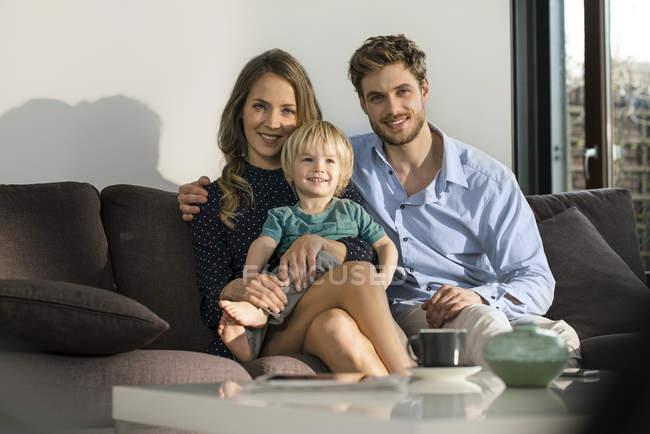 Портрет усміхнених батьків і сина, сидячи на дивані вдома — стокове фото