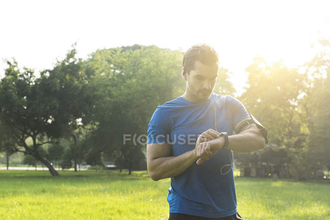 Runner nel parco urbano a controllare il suo smartwatch — Foto stock