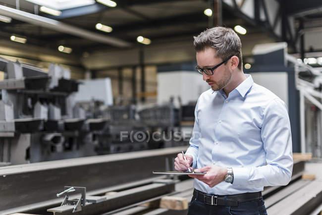 Homme utilisant une tablette sur le plancher de l'usine — Photo de stock
