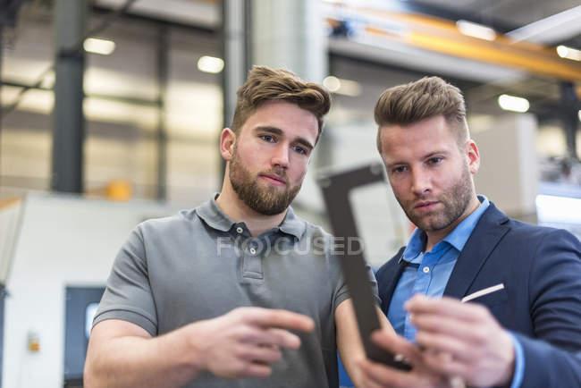 Employee and businessman examining workpiece on factory shop floor — Stock Photo
