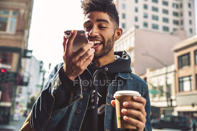 Retrato de jovem elegante com café e smartphone na rua — Fotografia de Stock