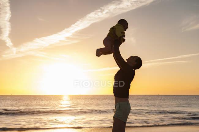Madre levantando a su hijita en la playa al atardecer - foto de stock