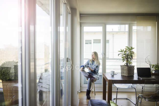 Donna con tavoletta seduta sullo sgabello guardando fuori dalla finestra — Foto stock