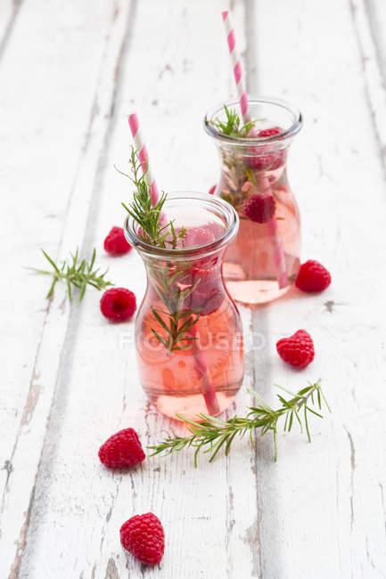 Dos botellas de vidrio de limonada de frambuesa casera aromatizada con romero - foto de stock