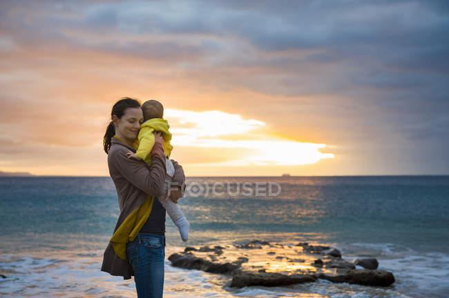 Mutter hält kleine Tochter am Strand bei Sonnenuntergang — Stockfoto