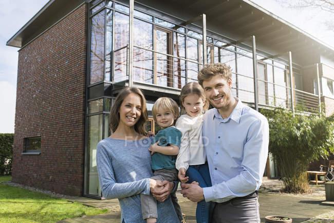 Retrato de familia sonriente frente a su casa - foto de stock