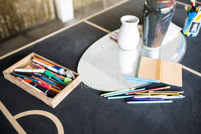 Crayons, pens and a notebook on a table in artist's studio — Stock Photo