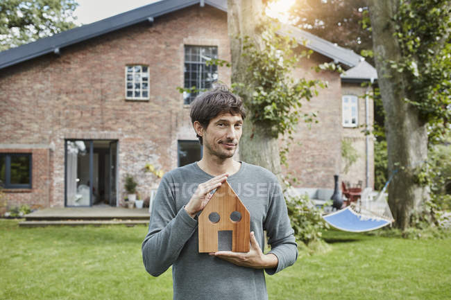 Portrait of man in garden of his home holding house model — Stock Photo