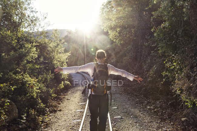 Grecia, Pilion, Milies, vista trasera del hombre con la mochila balanceándose a lo largo de los rieles del ferrocarril de vía estrecha - foto de stock