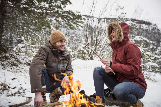 Happy couple on a trip in winter having a break at camp fire — Stockfoto