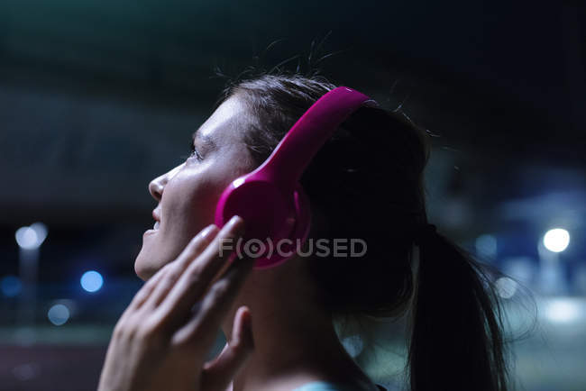 Happy young woman with pink headphones listening to music in modern urban setting at night — Stock Photo