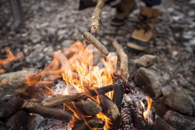 Gros plan de la saucisse se préparant sur le bâton sur le feu de camp — Photo de stock