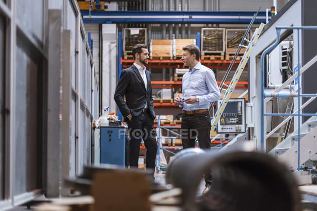 Два бизнесмена обсуждают на заводе — стоковое фото
