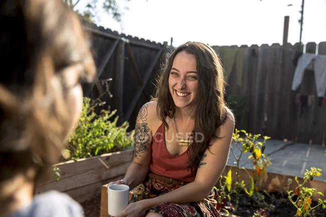Two happy young women talking in backyard — Stock Photo