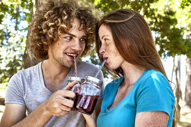 Sorrindo jovem casal tendo bebida na floresta — Fotografia de Stock