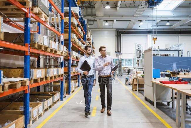 Two men walking in factory — Stock Photo