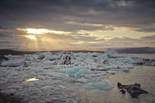 Islândia, sul de Islândia, lago da geleira de Joekulsarlon, icebergs e luz do sol através das nuvens — Fotografia de Stock