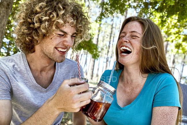Сміється молода пара, що випивають в лісі — стокове фото
