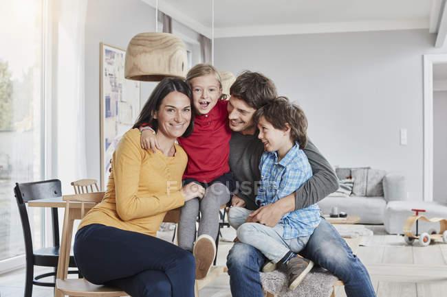 Портрет счастливой семьи с двумя детьми дома — стоковое фото