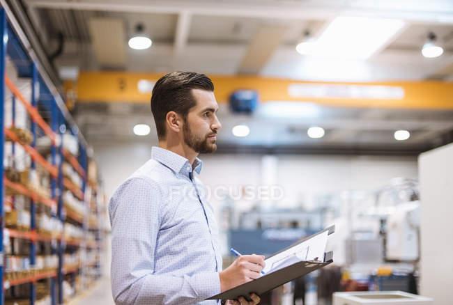 Geschäftsmann in Fabrik-Holding-Ordner — Stockfoto