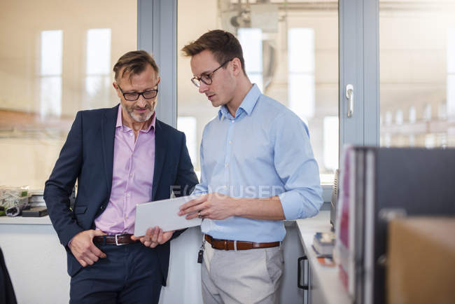 Two businessmen sharing tablet in office — Stock Photo
