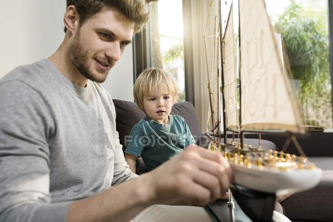 Батько і син дивлячись на іграшку модель корабля на дивані будинку — стокове фото