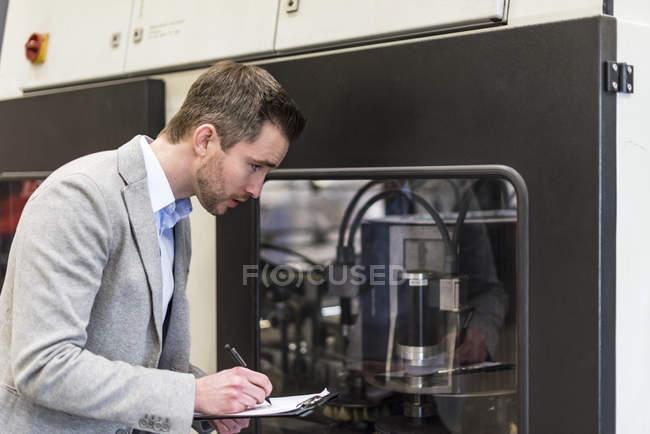 Geschäftsmann schaut sich Maschine an und schreibt auf Klemmbrett in Fabrik — Stockfoto