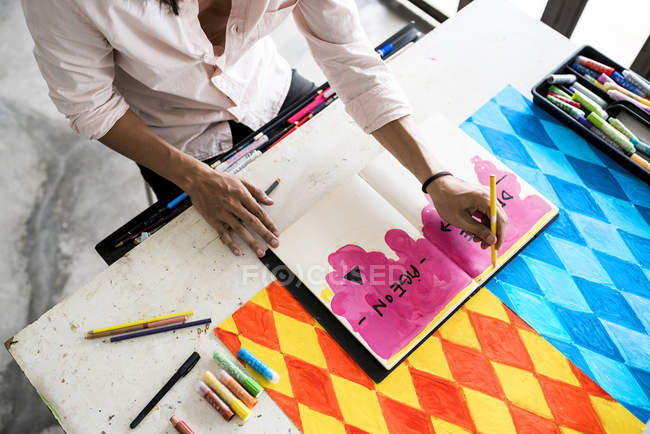 Artist drawing into notebook with his artwork on the table — Stock Photo