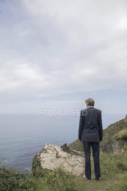 Uk, cornwall, gwithian, Geschäftsmann, der an der Küste steht und die Aussicht betrachtet — Stockfoto