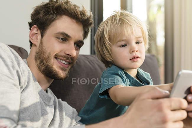 Батько і син дивлячись на смартфон на дивані вдома — стокове фото