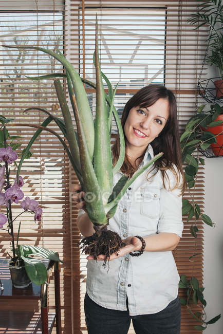 Portrait of smiling woman holding an aloe vera — Stock Photo