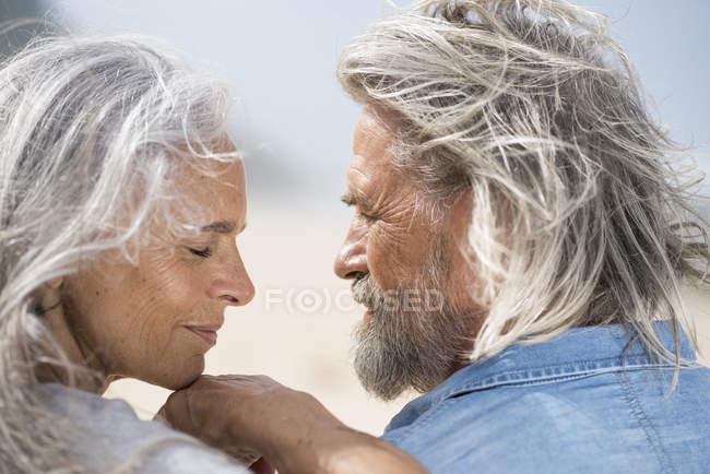 Liebevolles Seniorenpaar blickt sich am Meer in die Augen — Stockfoto