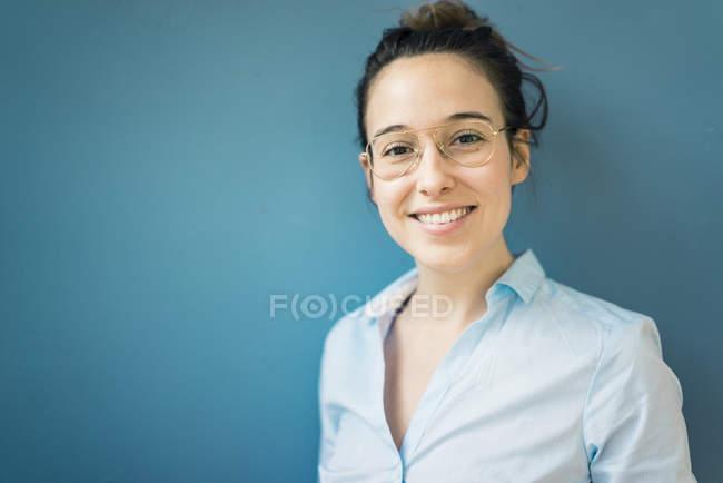 Портрет усміхнена молода жінка в окулярах перед синьою стіною — стокове фото