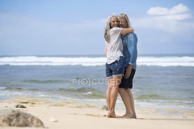 Ласковая пожилая пара, стоящая на пляже — стоковое фото