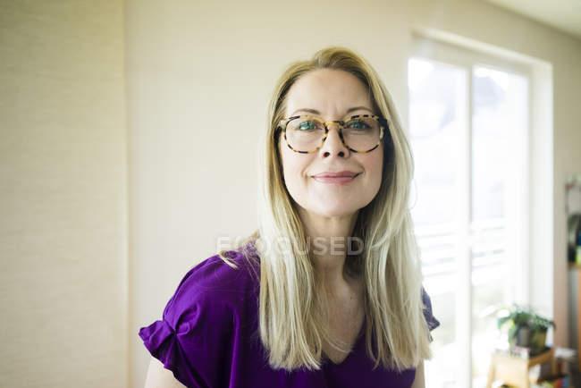 Retrato de mujer madura rubia sonriente con gafas - foto de stock