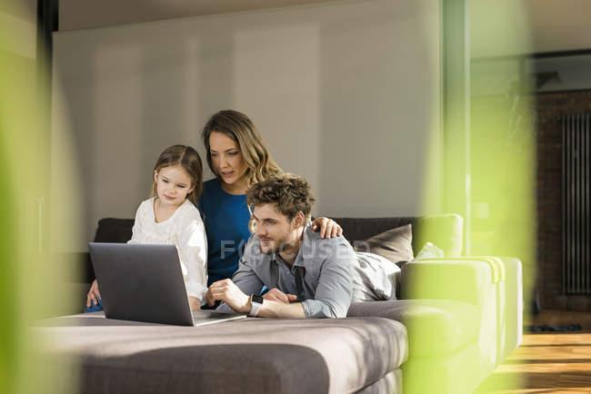 Famiglia che utilizza il computer portatile sul divano a casa — Foto stock