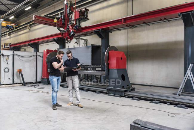 Двое мужчин с папкой, стоящими на полу фабрики — стоковое фото