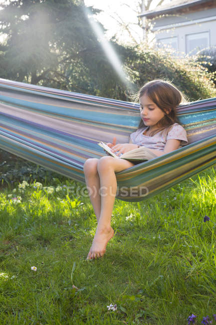 Little girl sitting on hammock in the garden reading a book — Stock Photo