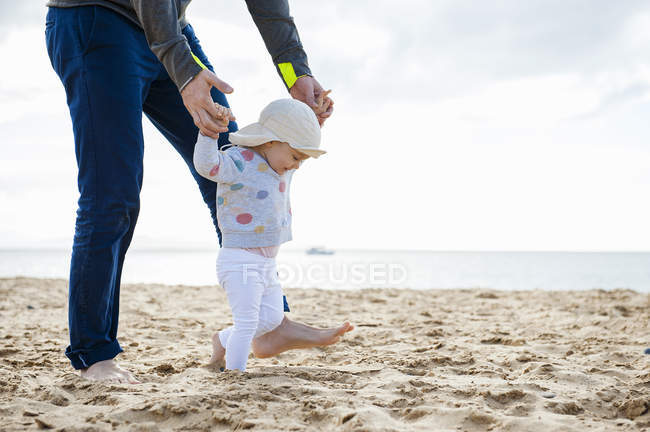 Espagne, Lanzarote, petite fille marchant sur la plage avec l'aide de son père — Photo de stock